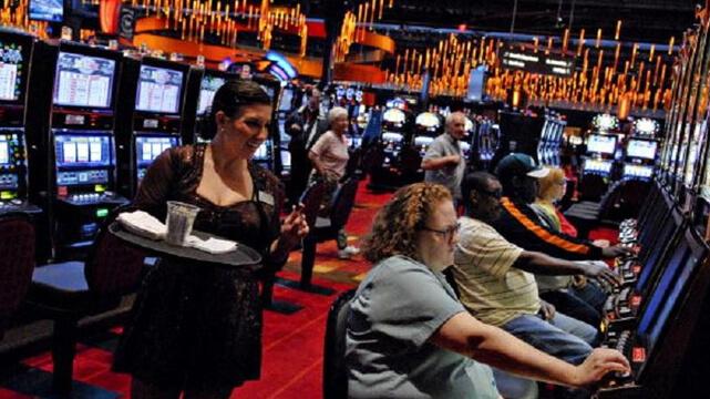 Leute, die im Casino Slots spielen und Getränke bekommen
